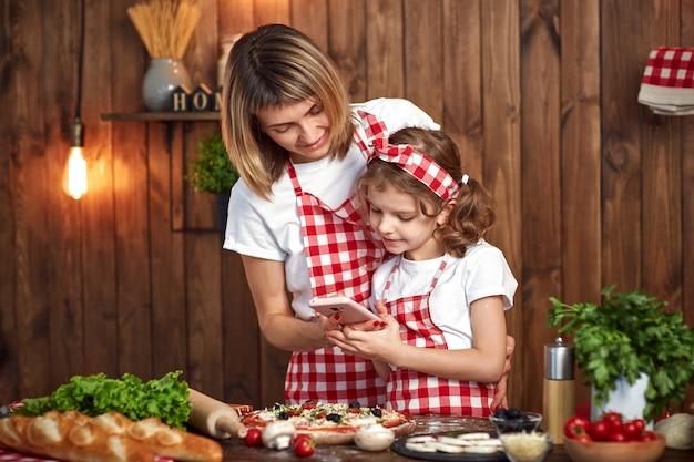 Moeder en dochter nemen foto's van gekookte pizza op smartphone
