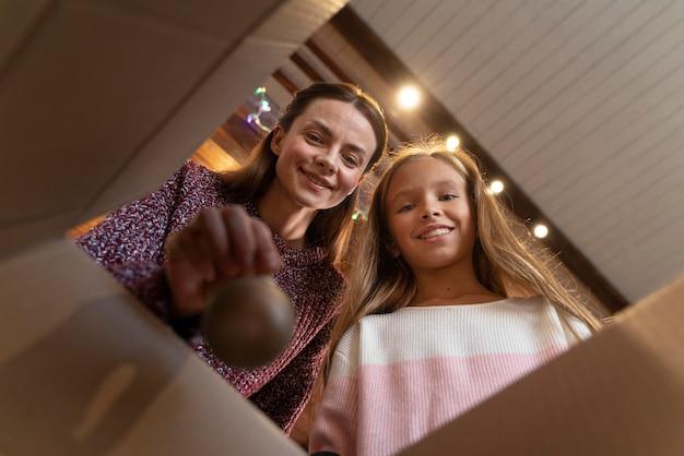 Moeder en dochter nemen ornamenten voor de kerstboom uit een doos