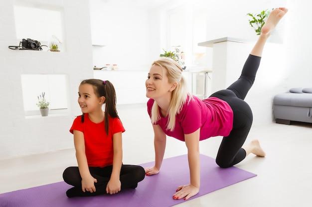 Moeder en dochter oefenen thuis online yogales tijdens de quarantaine-isolatieperiode tijdens de pandemie van het coronavirus. familie die samen online sport vanuit huis. gezonde levensstijl
