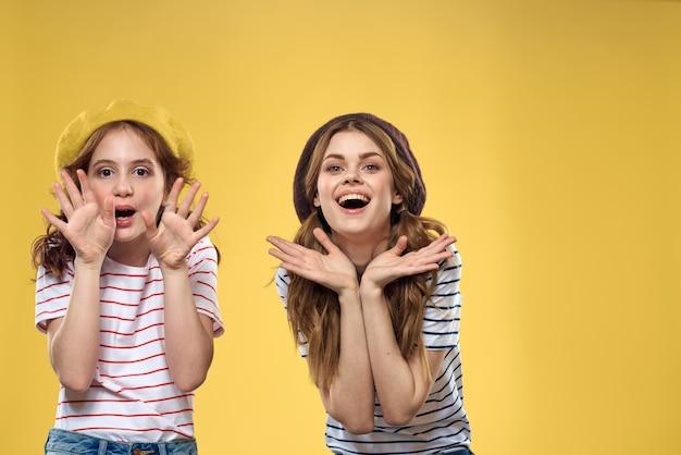 Moeder en dochter omarmen vreugde plezier jeugd levensstijl gele achtergrond