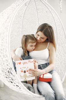 Moeder en dochter omarmen. zittend op een witte coconstoel.