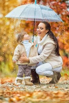 Moeder en dochter onder de paraplu verbergen zich voor de regen. gelukkige grappige familie met rode paraplu onder de herfstdouche. meisje en haar moeder genieten van regen. wandeling in het park.