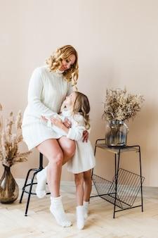 Moeder en dochter op beige achtergrond in witte sweaters