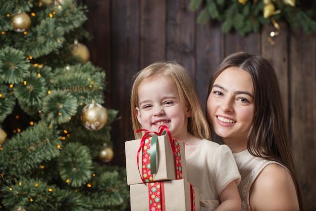 Moeder en dochter op de kerstboom op een houten achtergrond