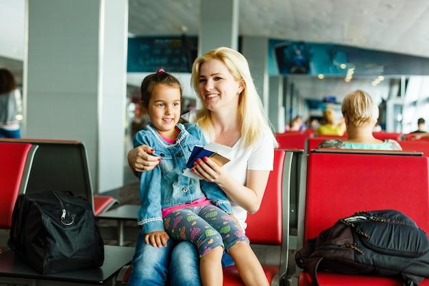 Moeder en dochter op de luchthaven in de wachtkamer