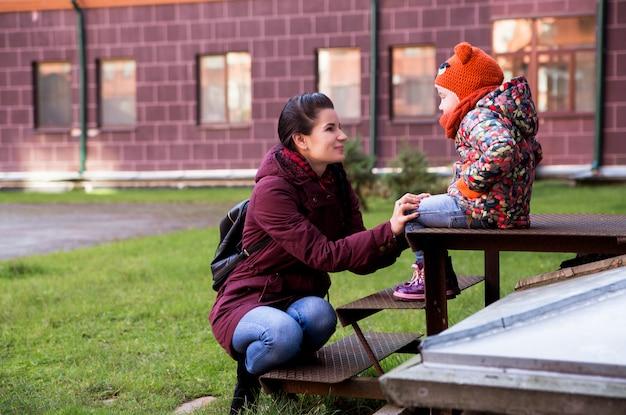Moeder en dochter op de veranda in de herfstweer