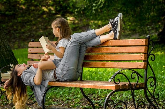 Moeder en dochter op een bankje lazen een boek in het park, het concept van familierelaties en familiewaarden