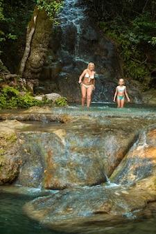 Moeder en dochter op een bergrivier onder een waterval in de jungle.turkije