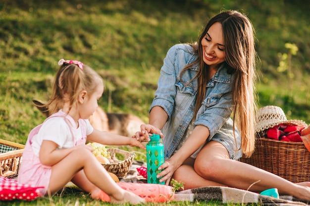 Moeder en dochter op een picknick met een hond