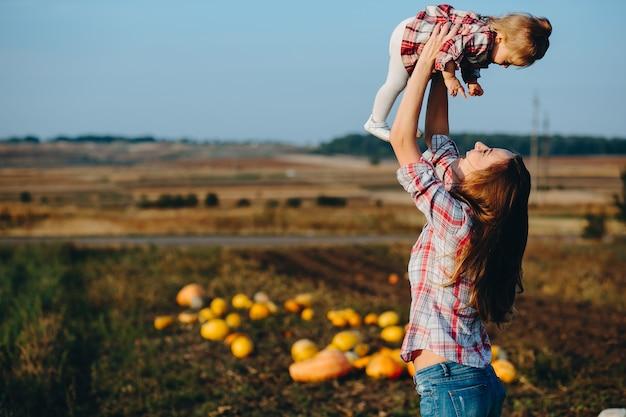 Moeder en dochter op een veld met pompoenen
