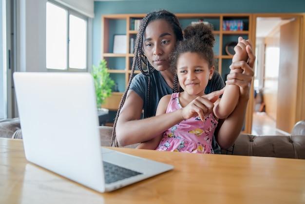 Moeder en dochter op een videogesprek met een arts voor een online medisch consult.