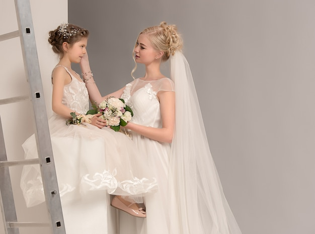 Moeder en dochter op haar trouwdag met witte jurk