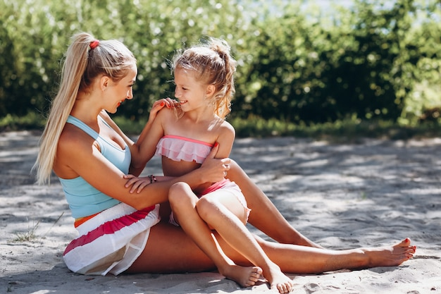 Moeder en dochter op het strand beoefenen van yoga