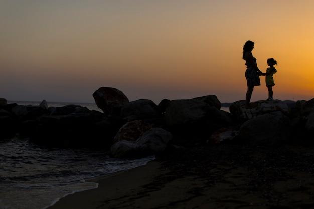 Moeder en dochter op het strand bij zonsondergang