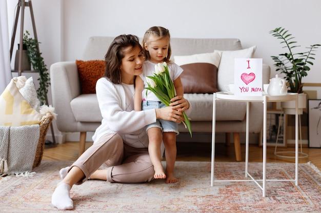 Moeder en dochter op vakantie met bloemen en een ansichtkaart thuis in de woonkamer