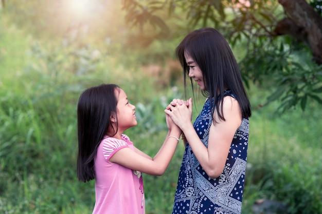 Moeder en dochter op zoek naar ogen en hand in hand met liefde