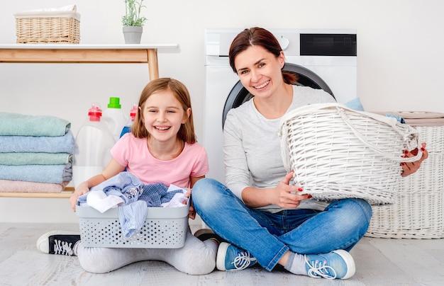 Moeder en dochter plezier tijdens wasserij zittend op de vloer met wasmanden in lichte kamer