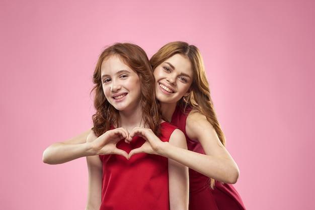 Moeder en dochter poseren hebben plezier en glimlachen, gelukkige familie, twee zussen