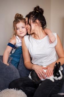 Moeder en dochter poseren samen met konijn