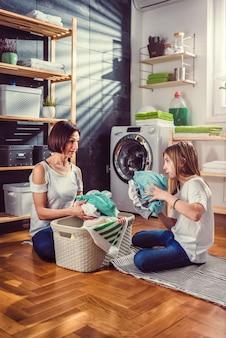 Moeder en dochter praten en sorteren wasgoed op de vloer