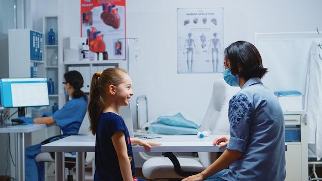 Moeder en dochter praten en wachten op de dokter in het medische kantoor tijdens het coronavirus. specialist in geneeskunde met beschermingsmasker die gezondheidsdiensten, overleg, behandeling in het ziekenhuis verleent.