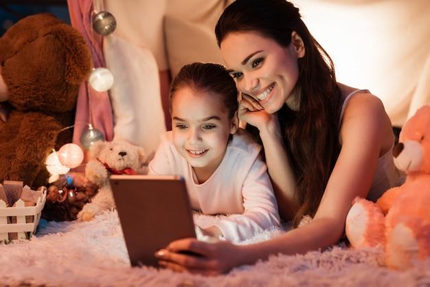 Moeder en dochter praten met vader op tablet.