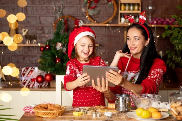 Moeder en dochter praten via videolink, groeten op een tablet in een donkere keuken met een kerstboom voor nieuwjaar of kerstmis, glimlachen en hebben samen plezier in een kerstmanhoed