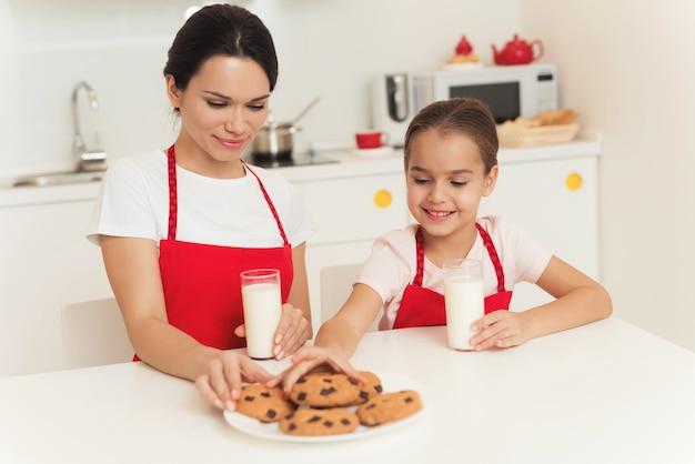 Moeder en dochter proberen koekjes die ze hebben gespeld.