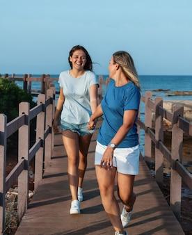 Moeder en dochter rennen op houten stoep aan zee bij zonsondergang een vrouw van middelbare leeftijd en tienerjongen