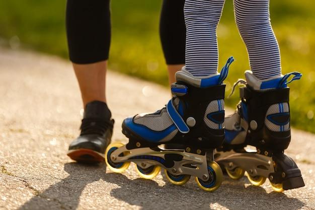Moeder en dochter rijden op rolschaatsen. meisje dat rolschaats leert, en valt