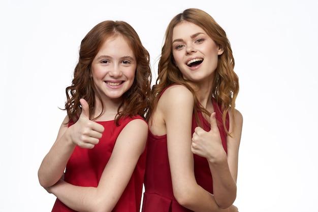 Moeder en dochter rode jurk knuffel familie vreugde vriendschap.