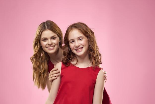 Moeder en dochter rode jurken leuke emoties geïsoleerde achtergrond Premium Foto