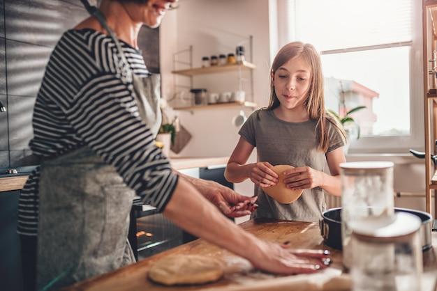Moeder en dochter rollend deeg voor appeltaart