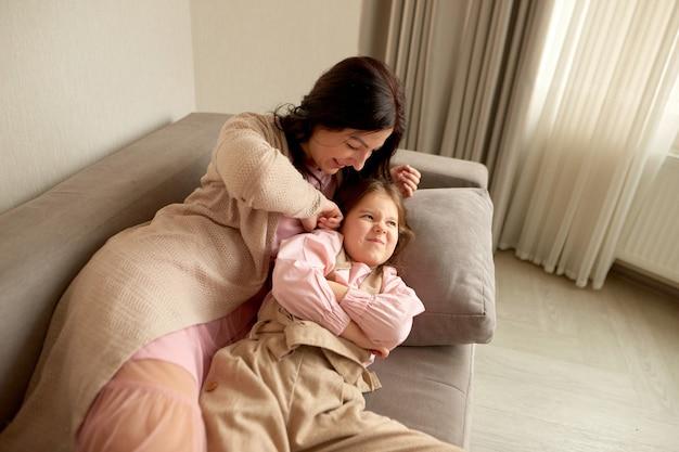 Moeder en dochter rommelen thuis. moeder kietelt dochter liggen op de bank in huis. dochter mokkend tegen moeder