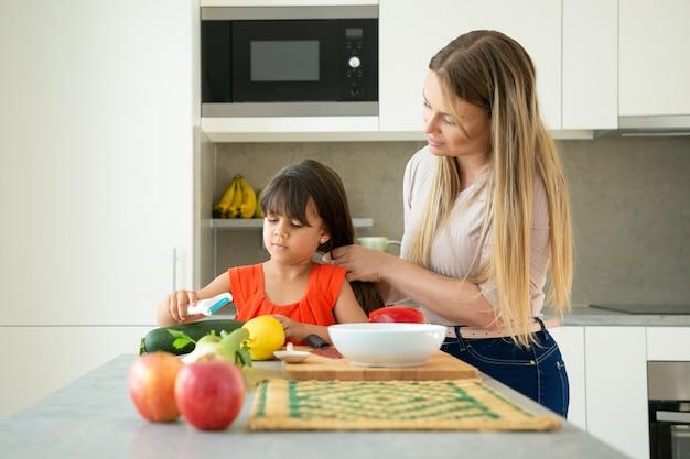 Moeder en dochter samen in de keuken. moeder vlechten meisjes lang haar, terwijl kind groenten pellen op de teller. familie koken concept