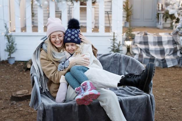 Moeder en dochter samen in de winter op de veranda