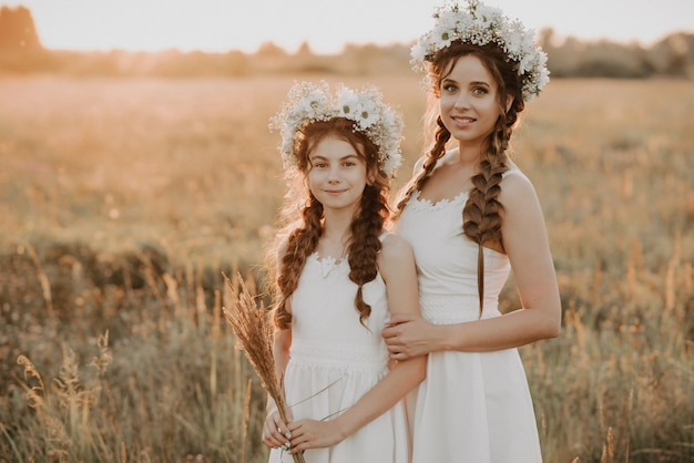 Moeder en dochter samen in witte jurken met vlechten en bloemenkransen in bohostijl op het gebied van de zomer bij zonsondergang