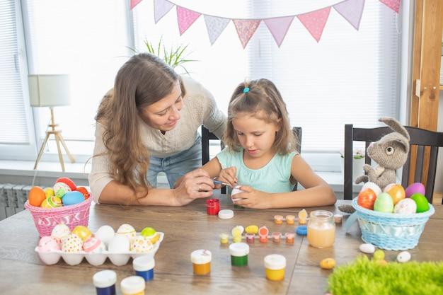 Moeder en dochter schilderen eieren voor de heldere vakantie van pasen. zitten voor blij met verf
