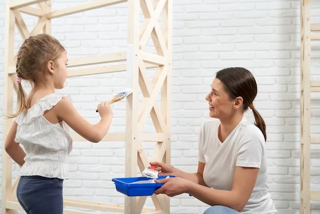 Moeder en dochter schilderen houten opbergstandaard