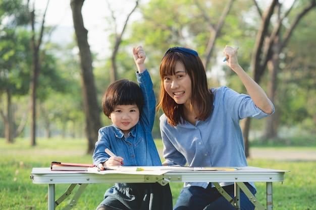 Moeder en dochter schilderen in het park op vakantie.