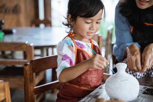 Moeder en dochter schilderen keramische pot