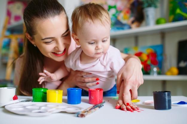 Moeder en dochter schilderen op canvas op de tekenschool.