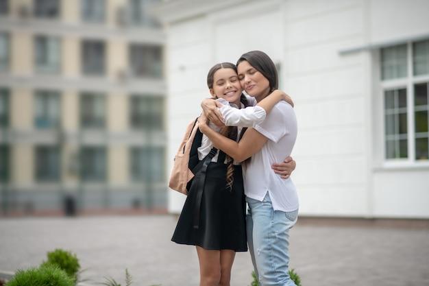 Moeder en dochter schoolmeisje met rugzak gelukkig lachend omarmen staande op schoolplein