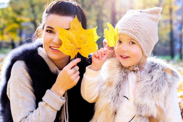 Moeder en dochter sluiten hun ogen met herfstbladeren