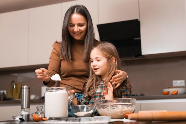 Moeder en dochter smaak aanbrengend kom voor het bereiden van gemberkoekjes