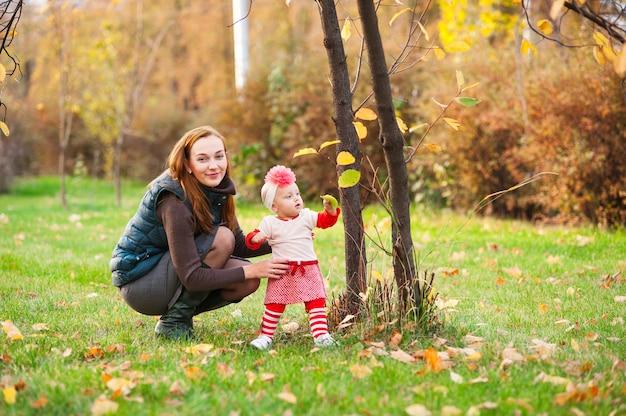 Moeder en dochter spelen in de herfst park.