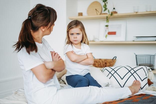 Moeder en dochter spelen, meisje is boos, ze leeft negatieve emoties. familie op bed in het lichte interieur