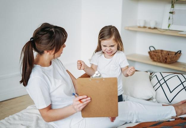 Moeder en dochter spelen, meisje is boos, ze leeft negatieve emoties. psychologische educatieve spelletjes voor kinderen