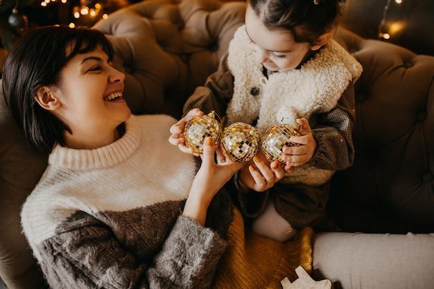 Moeder en dochter spelen met kerstboomballen thuis
