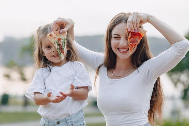 Moeder en dochter spelen met pizza in de natuur